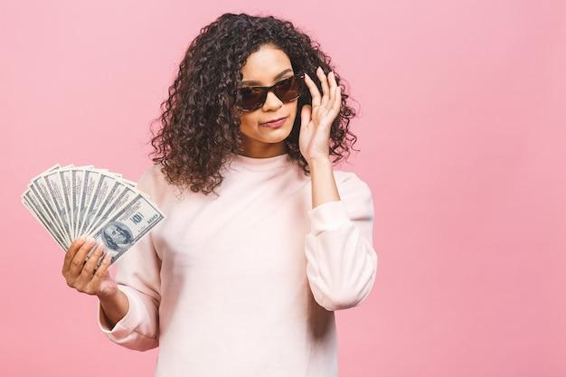 Классная богатая девочка! денежный победитель! удивленная красивая афро-американская женщина в случайном холдинге деньги в солнечных очках, изолированных на розовом фоне.