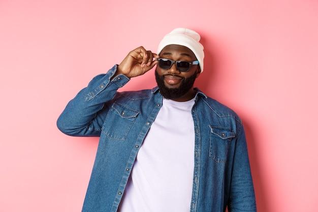 Uomo barbuto afroamericano fresco e impertinente, dall'aspetto fiducioso, toccando gli occhiali da sole e fissando la telecamera per favore, in piedi su sfondo rosa