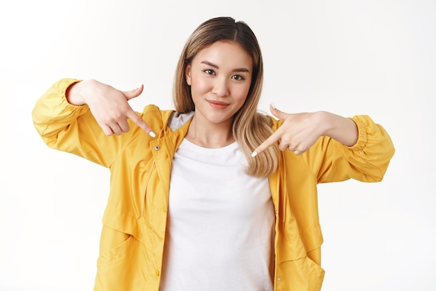 Fresco sfacciato di bell'aspetto hipster asiatico ragazza bionda assertivo alzare l'indice rivolto verso il basso sogghignando determinato emozioni positive sicure di sé che raccontano la scelta migliore proporre guardare in basso