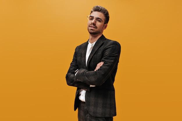체크 무늬 재킷과 흰색 티셔츠에 멋진 자신감 남자가 카메라를 찾습니다. 수염 난된 남자는 오렌지 벽에 팔과 포즈를 교차합니다.