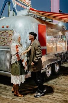遊園地内のフードトラックのそばに立っているクールな年配のカップル