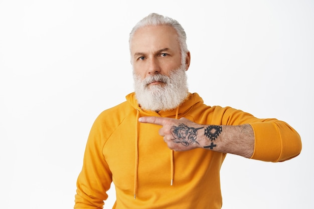 Cool senior hipster man with tattoos pointing left at copy space, showing advertisement, grandad with long beard wearing stylish hoodie recommending click link, white wall