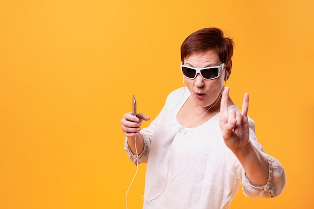 Cool senior woman listening rock music