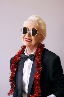 Cool senior woman in tuxedo and sunglasses at the party