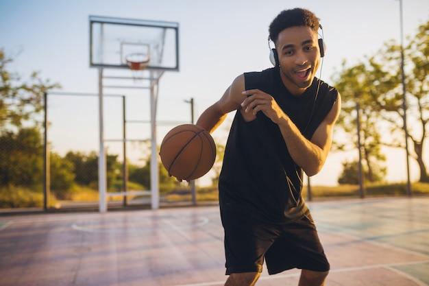 Крутой улыбающийся темнокожий мужчина занимается спортом, играет в баскетбол на рассвете, слушает музыку в наушниках, активный образ жизни, летнее утро