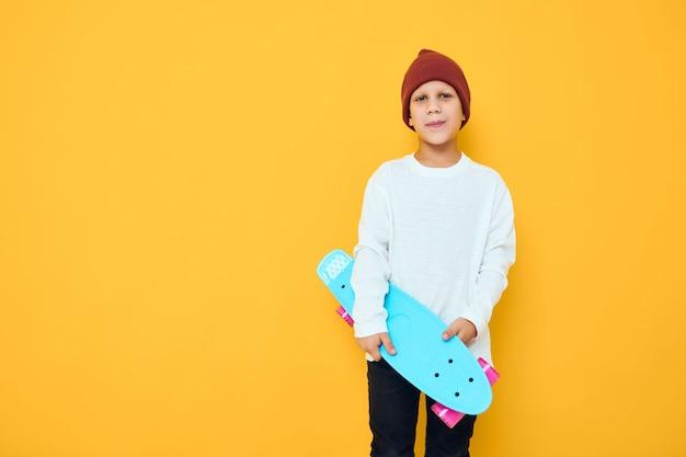 Cool smiling boy casual blue skateboard studio posing