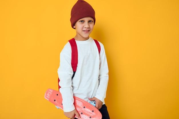 彼の手の孤立した背景に赤い帽子のスケートボードでクールな笑顔の少年