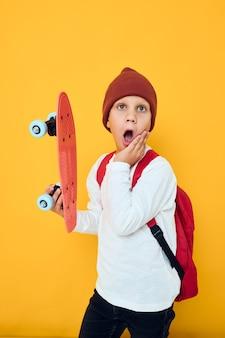 彼の手の黄色の色の背景に赤い帽子のスケートボードでクールな笑顔の少年