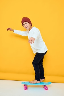 Cool smiling boy with red backpack blue skateboard yellow color background