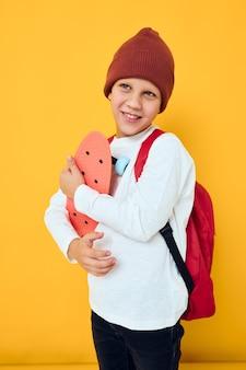 赤いバックパックとクールな笑顔の少年赤いスケートボードの孤立した背景