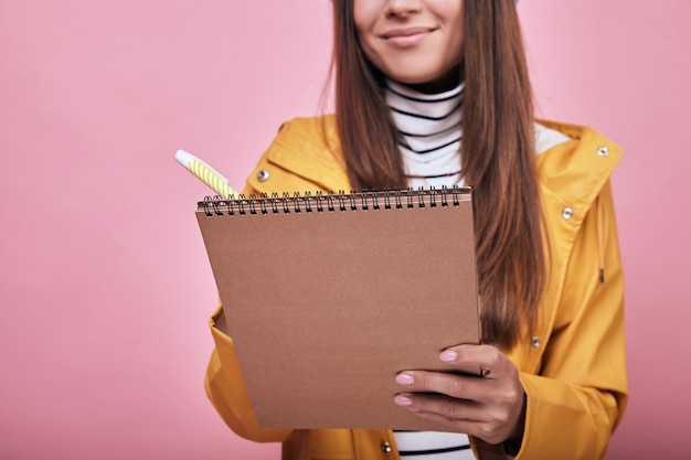 Cool smiling student standing with a notebook and pen in hands
