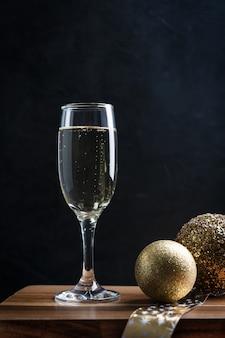 Прохладное игристое шампанское в высоком бокале с рождественскими золотыми шарами на деревянной барной стойке
