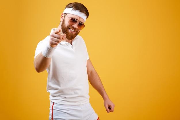 Крутой спортсмен в темных очках указывает на тебя