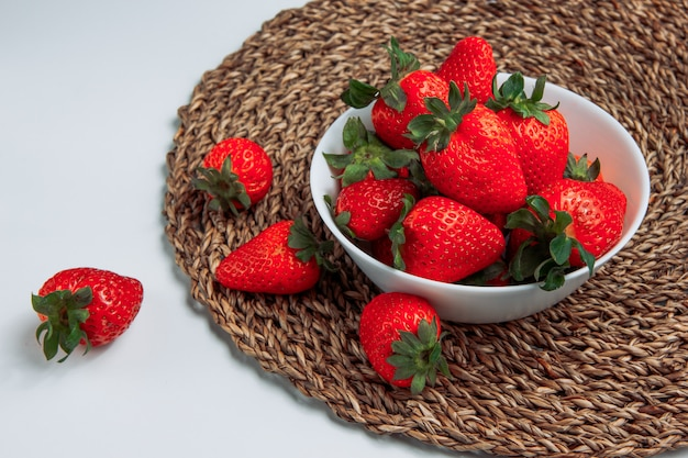Cool strawberries in a white bowl on a grey gradient and round placemat background. side view.