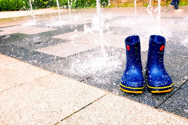 A cool stream of water is coming out of the fountain. there are blue rain boots on the sidewalk block.