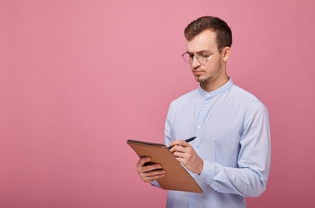 Классная студентка в бледно-голубой рубашке в очках с коричневым флипчартом и черной шариковой ручкой пишет