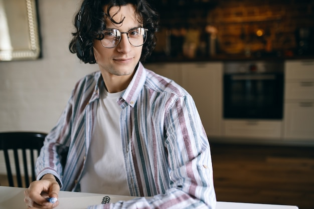 Cool student in stylish glasses doing home assignment at desk, making notes, listening to music via wireless headphones. attractive young male artist with earphones sketching in notebook, smiling