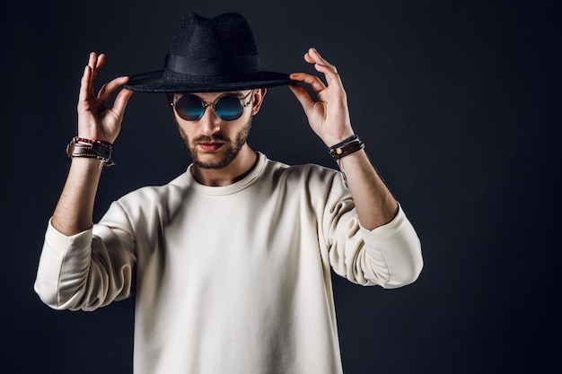 Cool stylish handsome man wearing sunglasses holding hat