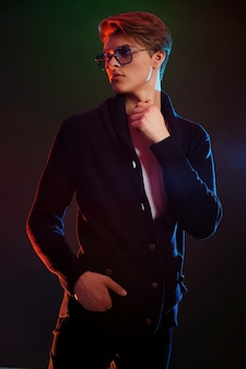 Крутой стильный мужчина в черной куртке и солнцезащитных очках