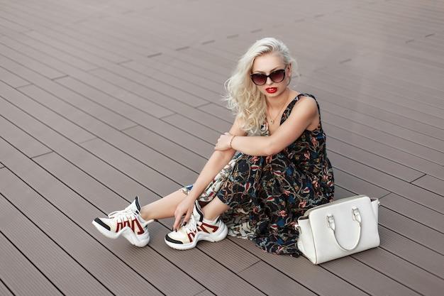 パターンとバッグと靴のファッショナブルなドレスのサングラスをかけたクールでスタイリッシュな女性は、デッキの木製の床に座っています