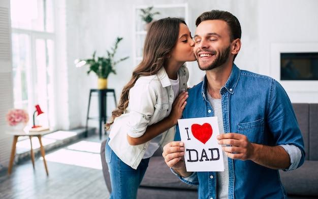 Классный сюрприз от дочери. я люблю тебя, папа. красивый молодой человек дома со своей маленькой милой девушкой. с днем отца