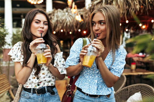Cool tanned brunette and blonde women in denim pants and floral stylish blouses walk outside in good mood and drink lemonade