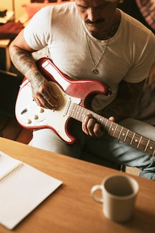 Cool tattooed man playing a guitar in a studio