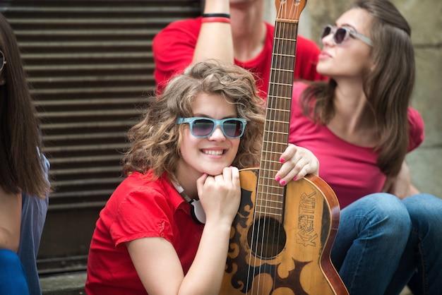 ギターとポーズを取るクールな十代の少女