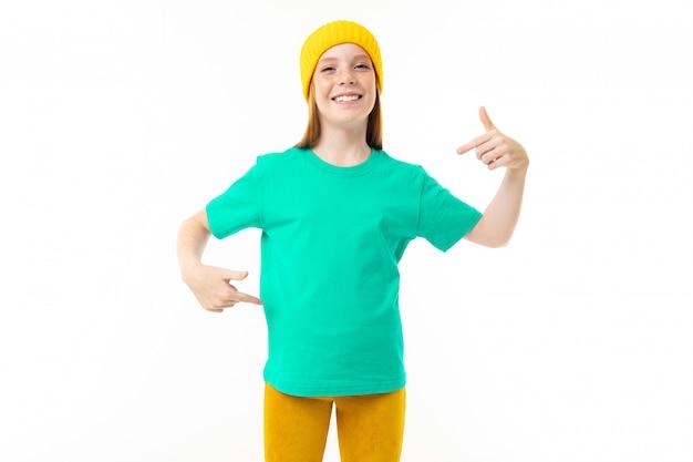 赤い髪、青いtシャツ、白い背景で隔離の黄色い帽子を持つクールなティーンエイジャーの女の子