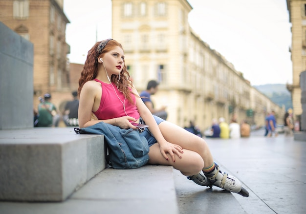Cool teenager sitting in the street, listening music