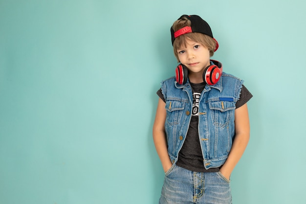 A cool tenager boy in denim jaket and shorts, red earphones, black cap, stands in front of the camera and keeps his hands in pockets, isolated on blue background