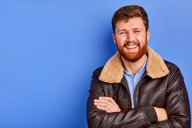 冬や秋のコートでクールなトレンディな男性が腕を組んで立って、笑顔でカメラにポーズをとる
