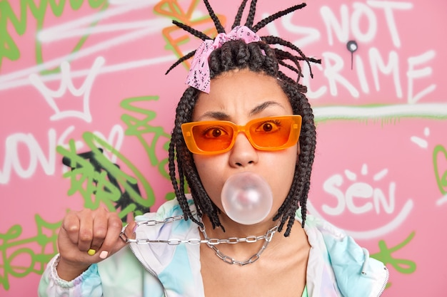髪の三つ編みを持つクールなトレンディな女性は、噛むガムを吹くファッショナブルな服を着て首にぶら下がっている金属チェーンを保持します