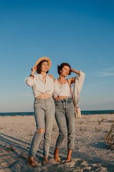 멋진 두 젊은 여성이 일몰 해변에서 재미, 게이 레즈비언 사랑 로맨스
