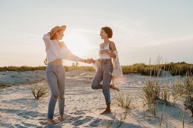 サンセットビーチで楽しんでいるクールな2人の若い女性、ゲイレズビアンの恋愛