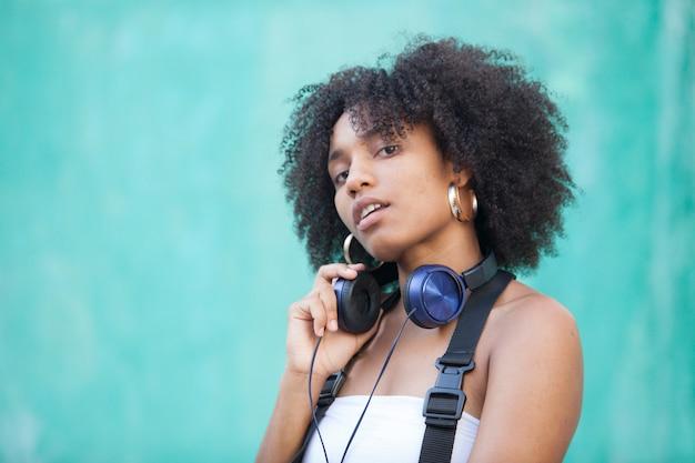 クールな都市の黒人女性が路上で音楽を聴く