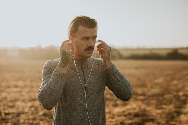 Крутой городской мужчина слушает музыку во время тренировки