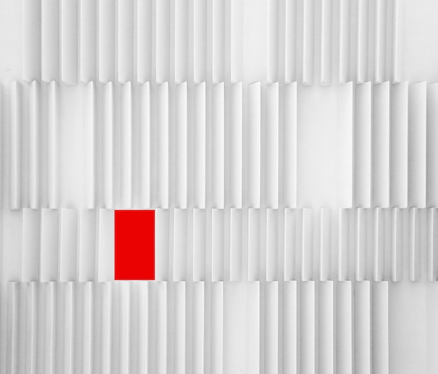 A cool white textured modern wall with a red different shaped rectangle - diversity concept
