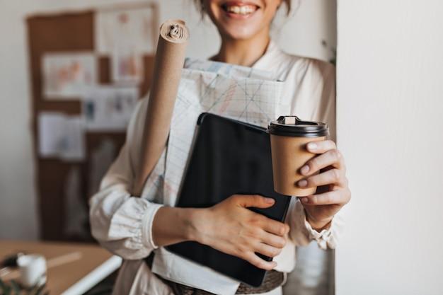 クールな女性は、ドキュメントとコーヒーカップを保持します