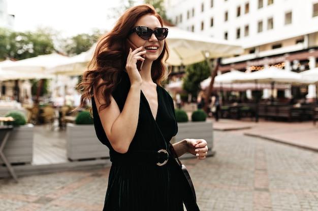 暗いドレスを着たクールな女性が電話で話します