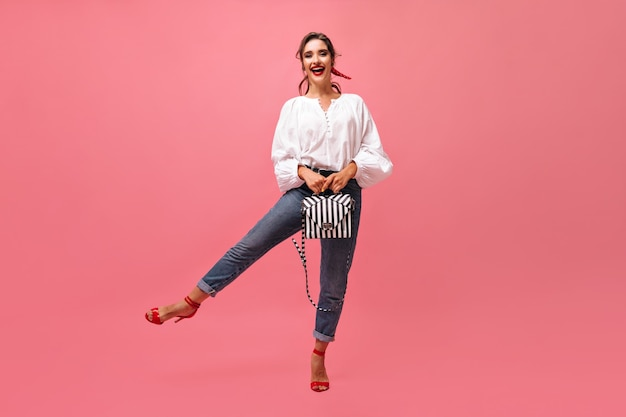 ピンクの背景にジーンズとブラウスのバッグを保持しているクールな女性。赤い口紅と髪に包帯を巻いたスタイリッシュな女の子が楽しんでいます。