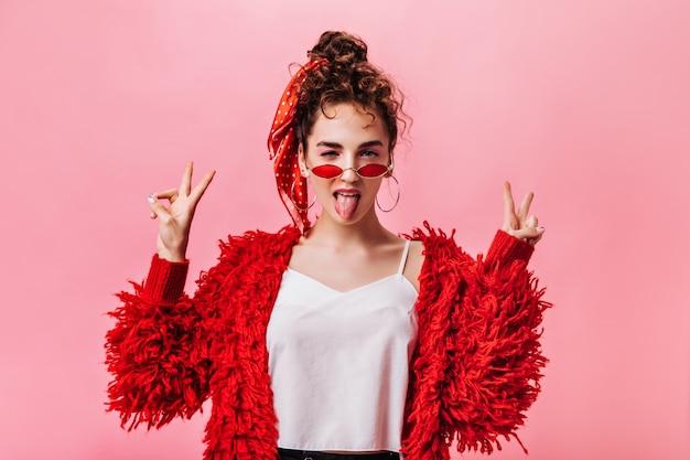 Крутая женщина в красном пальто и очках показывает знак мира на розовом фоне