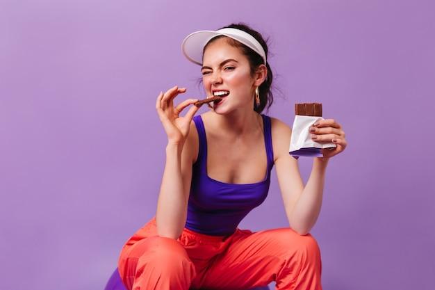 80 년대 스타일의 스포츠 복장을 입은 멋진 여성이 보라색 벽에 앉아 맛있는 밀크 초콜릿 바를 물었습니다.