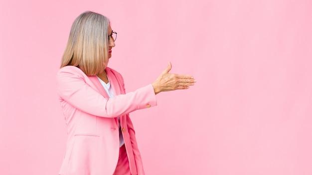 クールな女性の笑顔、あなたに挨拶し、成功した取引、壁に対する協力の概念を閉じるために握手を提供します
