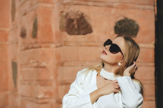 자연 태양광과 함께 거리에서 포즈를 취하는 니트 스웨터를 입은 멋진 여성. 텍스트를 위한 공간