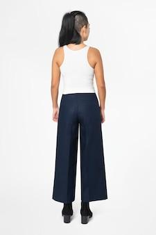 Bella donna in canottiera bianca e pantaloni a trapezio neri street fashion vista posteriore