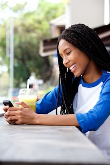 Cool young african girl using smartphone at outdoor cafe