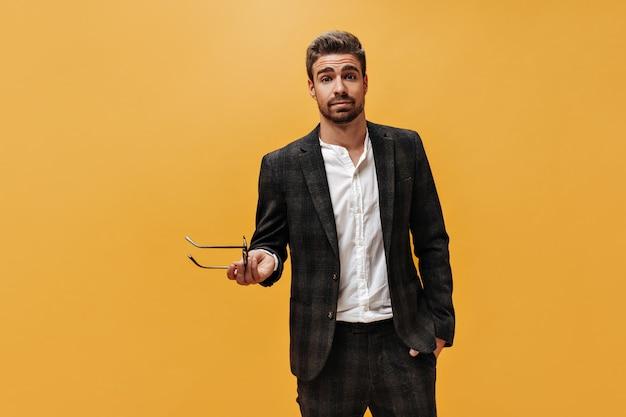 체크 무늬 재킷, 바지 및 흰색 셔츠에 멋진 젊은 수염 난 남자가 카메라를 들여다보고 주황색 벽에 안경을 들고 있습니다.