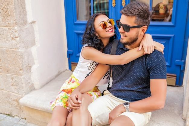 Крутая молодая красивая хипстерская влюбленная пара сидит на улице старого города