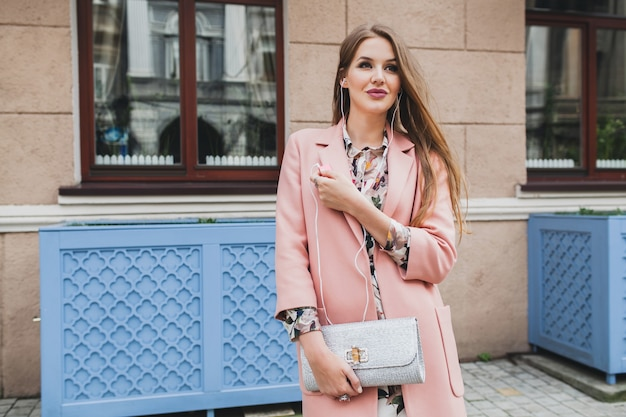Cool young beautiful stylish woman walking in street in pink coat, holding purse in hands, listening to music